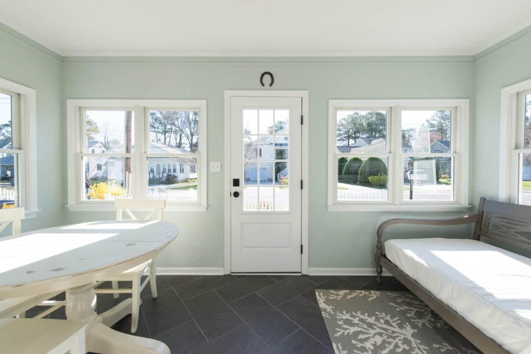 Kent Renovation Sunroom with Dark Floor Tiles, White Distressed Table, Wood Bench Seat and Light Sea Foam Wall Paint