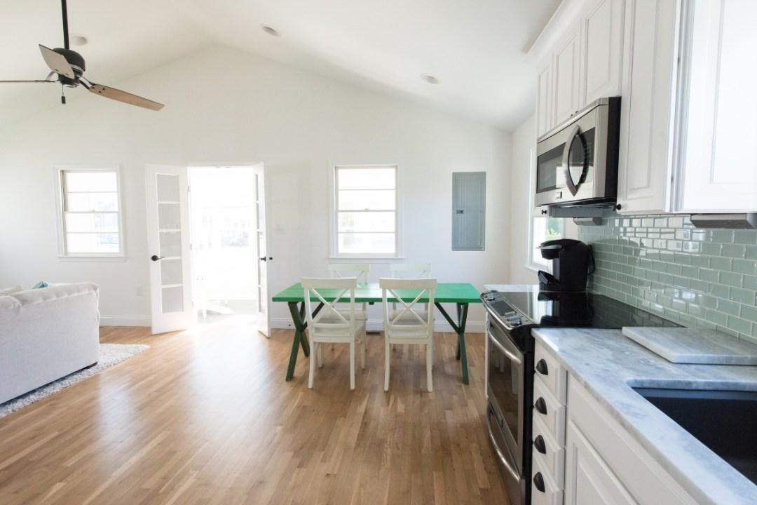 Kent Renovation Bethany Beach, DE White Room with Green Dining Table, Wood Flooring, Light Sea Foam Glass Glossy Tiles Backsplash