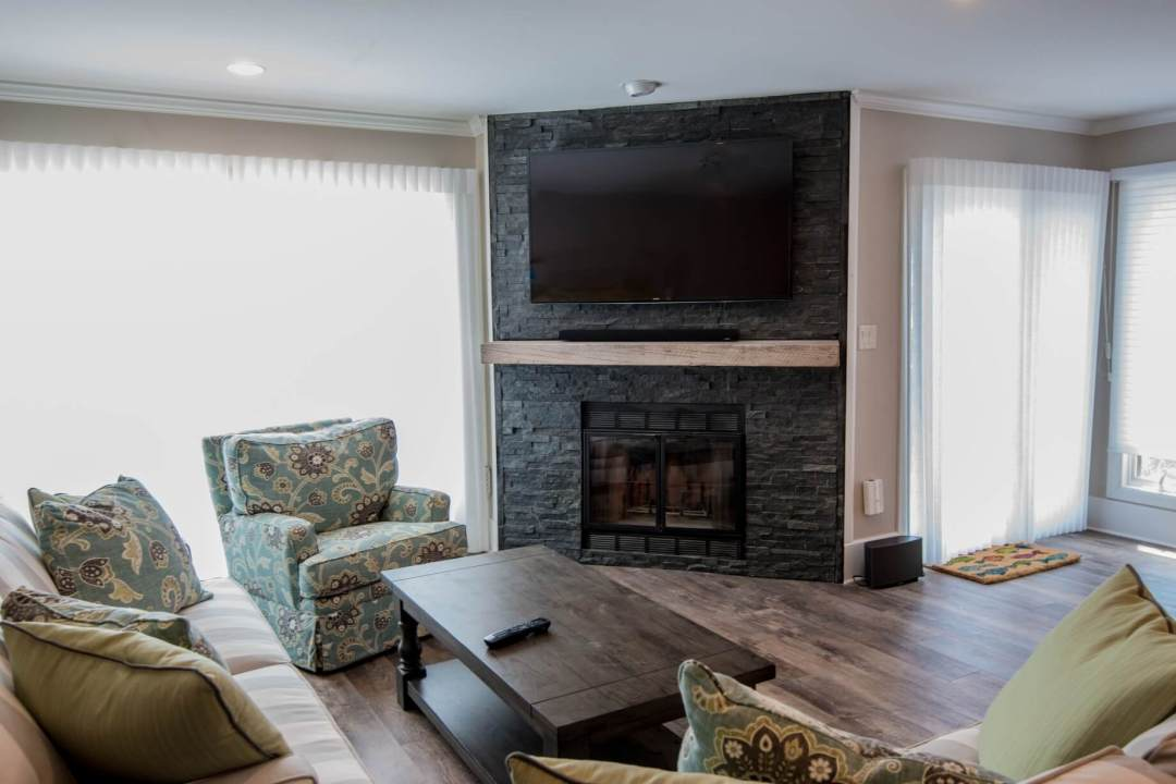 Kings Grant Renovation Vol.2 with Wall Mount TV Above Dark Stone Fireplace, Hardwood Flooring and Dark Wood Coffee Table