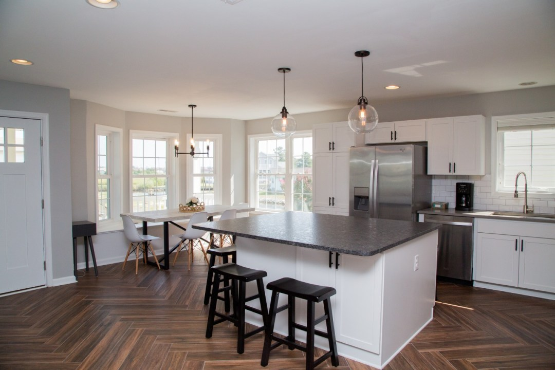 Kitchen with White Cabinets, Center Isle, Dark Granite Countertop and Pendant Lighting