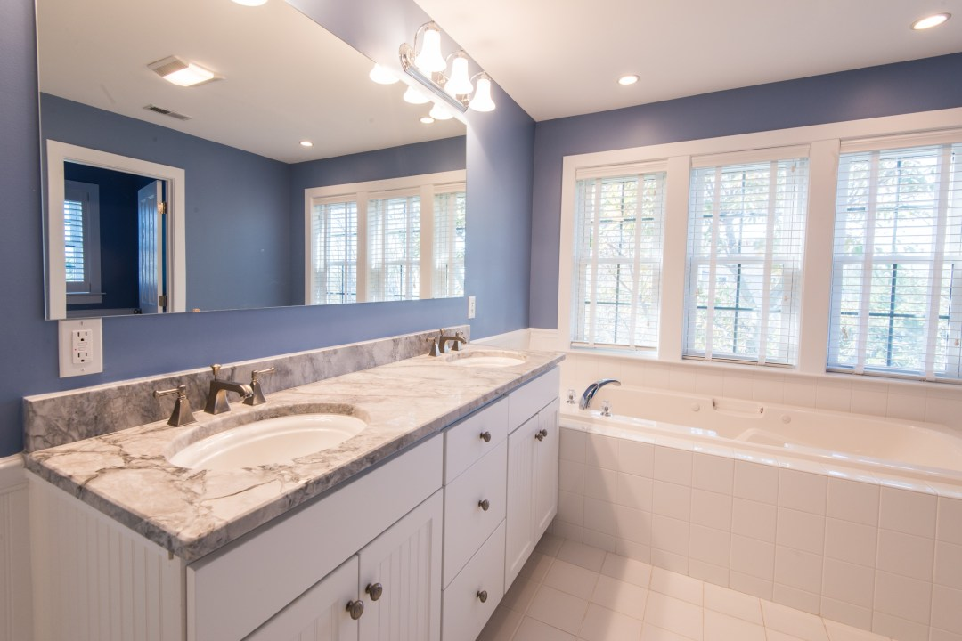 Bathroom Remodel in Ocean Ridge, Bethany Beach DE with Large Mirror, White Wood Vanity, Light Grey Countertop and Bathtub