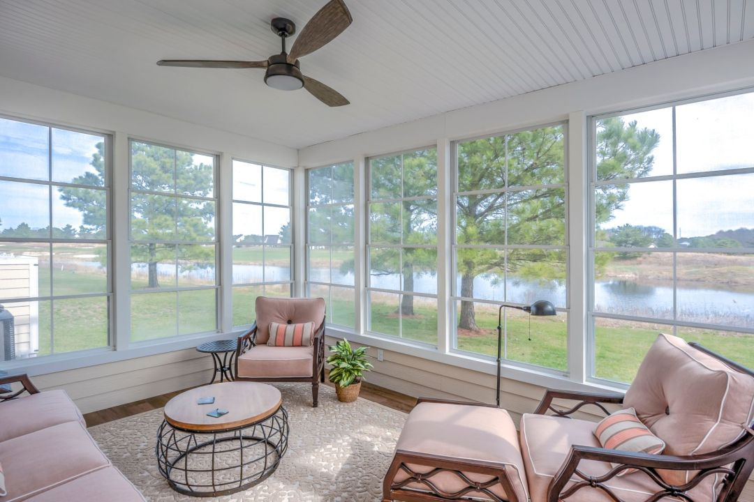 October Glory Exterior in Ocean View DE - Sunroom with Beige Soft Furniture and Vertical Sliding Windows