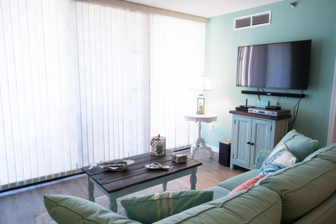 Sea Colony Condo Renovation Bethany Beach, DE Living Room with Turquoise Color Large Sofa and Dark Wood Floor