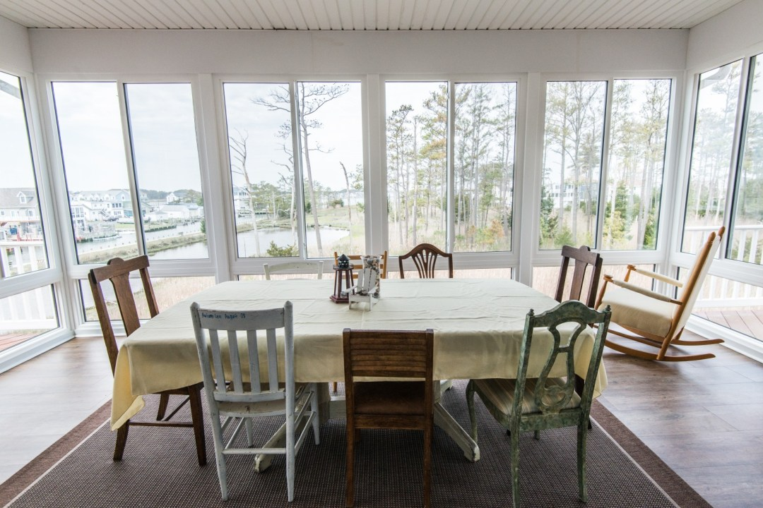 Whitesview Court Sunroom Vol.2 in Ocean View DE Between Two Decks with COREtec Plus Flooring and Large Table