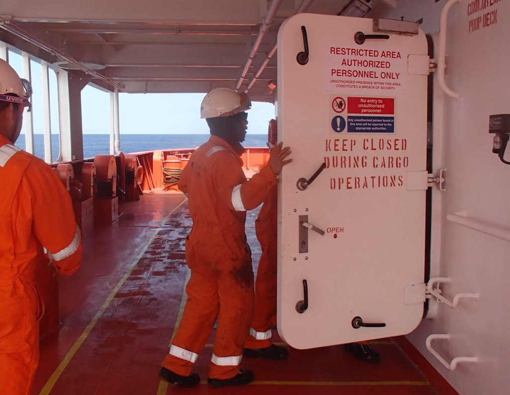 """Crew entering the watertight door marked with """"Restricted Area""""."""
