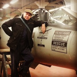 In a flat cap. And by an aeroplane we discovered on set.