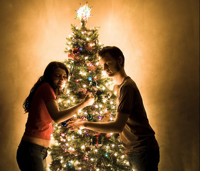 couple lovingly hugging a christmas tree