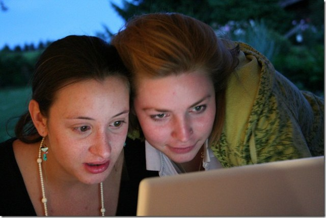 Two young women check out a Facebook page on their laptop