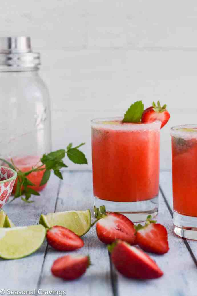 lime rickey gin drink in a glass with strawberries and limes