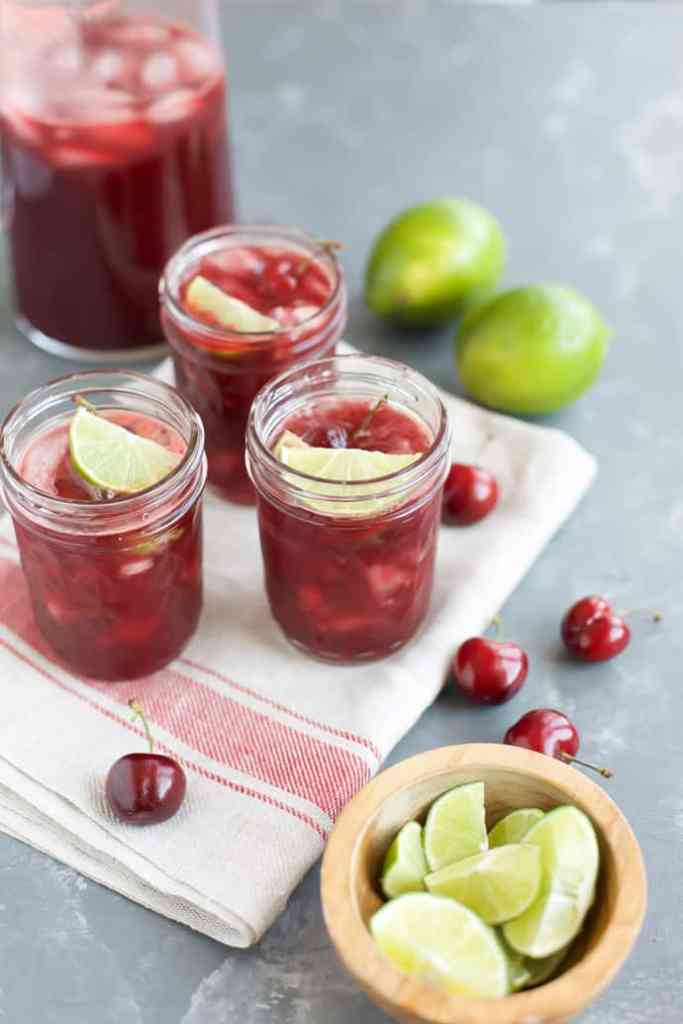 Cherry Margaritas in three glasses with limes