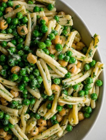 Overhead close up of green goddess pasta salad with peas, chickpeas and herb dressing.