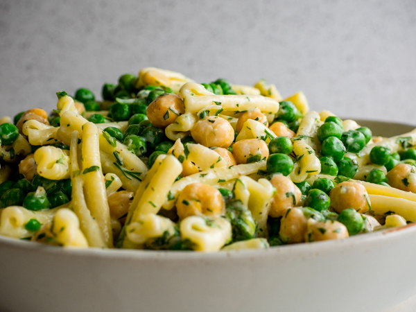 Close up of green goddess pasta salad with peas and chickpeas and creamy yogurt dressing.