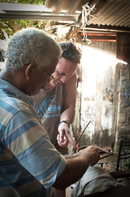 Blacksmith Ernesto Muñoz shows Northwest native Del Morris how to craft a scroll out of metal in his workshop in Cartagena. (Photo by Wesley Tomaselli)
