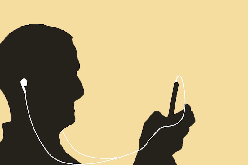 Man with headphones getting Hindi listening practice on a mobile device.