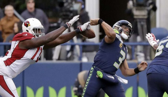 Seattle Seahawks quarterback Russell Wilson has his pass attempt blocked by the Arizona Cardinals defender (Photo Seattle PI)