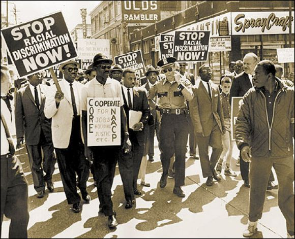 The Rev. Mance Jackson (center, next to police officer) leading demonstrators in downtown Seattle Seattle Post-Intelligencer