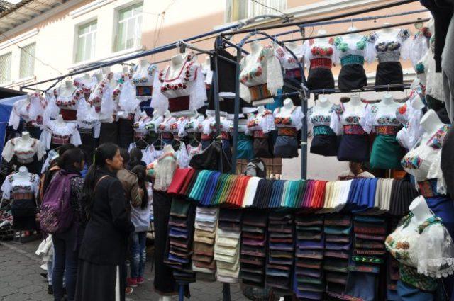 Buying traditional indigenous dress, Otavalo market