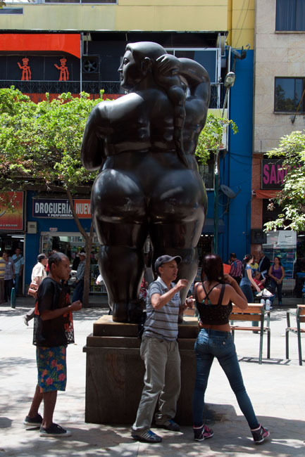 Lady of the evening with Botero statue in Medellín's red light district