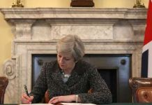 Theresa May mentre firma la notifica su Brexit