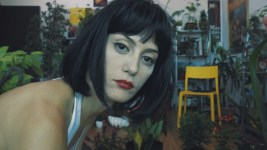 Close-up of a woman's face with red lipstick and numerous house plants behind her