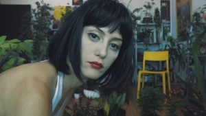 face of a woman with red lipstick and a bob with numerous house plants behind her.
