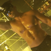 Still image from the short film In a Strange Room. A shirtless, oiled and very muscular man is dancing in a club.