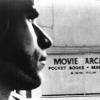 Still image from LA Plays Itself. Black and white image of a clean shaved man's profile, with a Movie Arcade sign in the background.