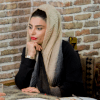 Still image from the documentary Red Liptick, showing Masoumeh wearing a headscarf resting her shin on her hand, with bright red lipstick on her lips..