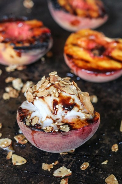 Easy Grilled Peach topped with scoop of vanilla ice cream and granola drizzled with Balsamic Glaze on pan