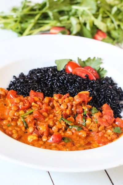 Bowl of gluten free, vegan Creamy Coconut Lentil Curry with black rice, tomatoes and cilantro