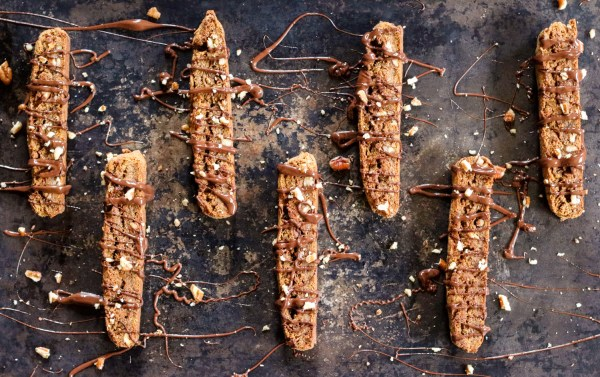 Pan of Vegan, gluten free Pumpkin Pecan Biscotti drizzled with dark chocolate sprinkled with nuts