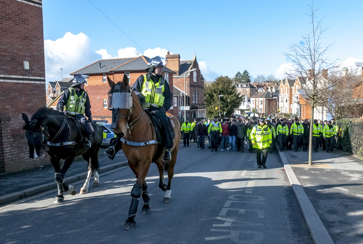 Devon and Cornwall Police escort Plymouth football fans during the police operation at the League 2 football match between Exeter City FC and Plymouth Argyle FC. Image: Clive Chilvers / Shutterstock.com