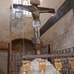 Crucifix standing over piece of rock of Calvary (Seetheholyland.net)