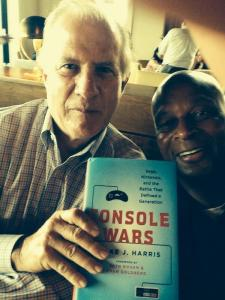 """Tom Kalinske and former NFL superstar Ronnie Lott take a photo holding the """"Console Wars"""" book."""