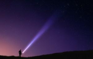 Silhouette eines Menschen gegen die rot-blaue Dämmerung. Er leuchtet mit einer Taschenlampe mit deutlich sichtbarem Strahl schräg nach oben in den Himmel.