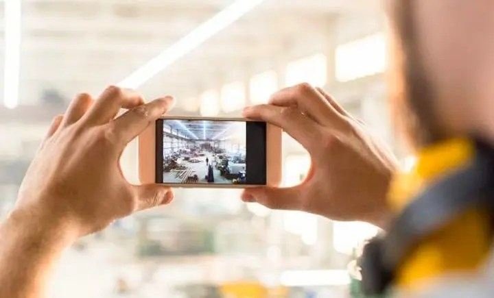 person testing the camera function on a used smartphone