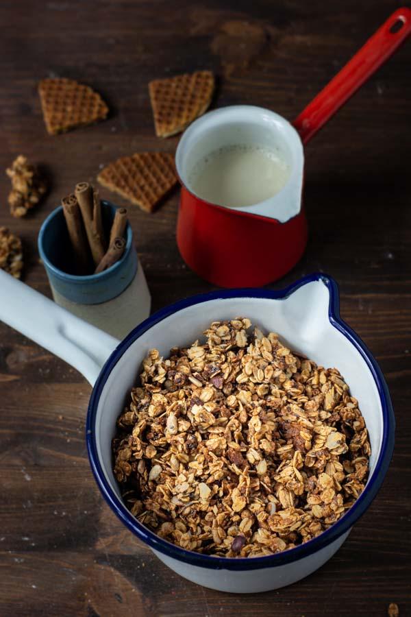 Eine Tpf Granola auf einem Tisch, dazu Sojamilch und Zimtstangen.