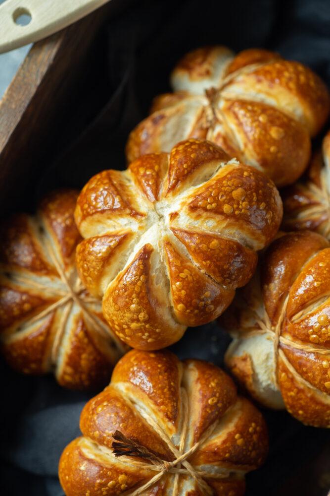 A couple of pumpkin shaped pretzel rolls in a wooden box.