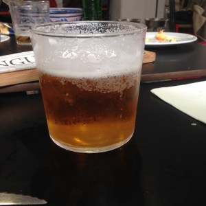 small beer with cheese plate in the background