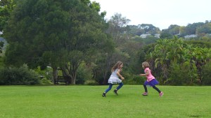 A game of chase, mackenzie and quinn run on the green lawn of Kristenbosh Gardens