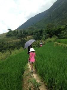 Chi helps Quinn navigate a narrow ledge through the rice field.