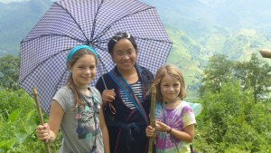Chi poses with Mack and Quinn holding her blue and white checkered umbrella rice fields in background