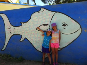 Mackenzie and Quinn stand in front of a blue wall with a big white fish painted on it.