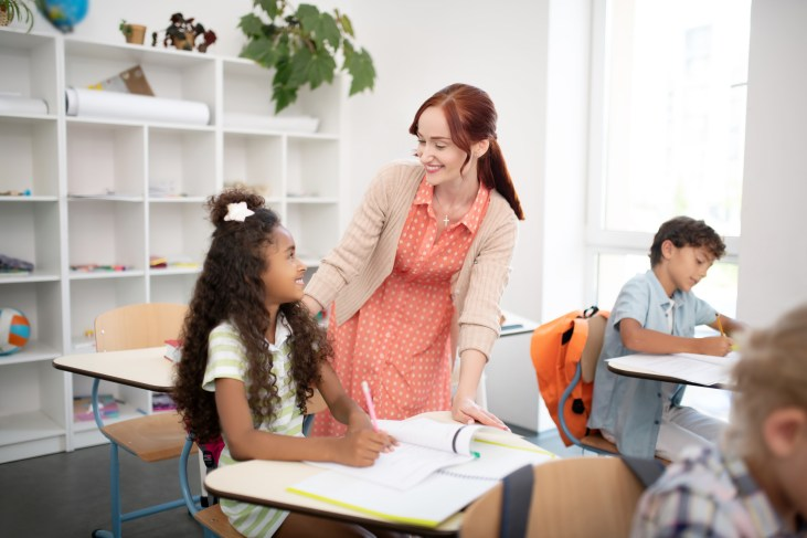 Curly dark-haired girl feeling good while speaking with teacher