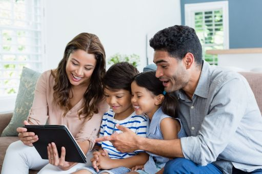 Canva - Parents and kids using digital tablet in living room