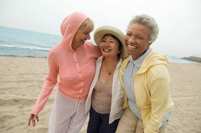 Three women smiling by the beach