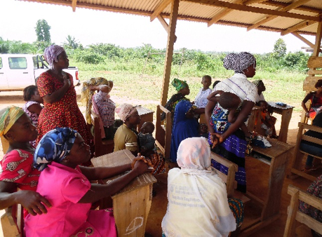 group of women gather under hut for microcredit training