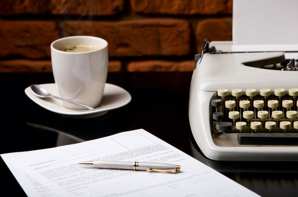 Once upon a time... Old fashioned morning scene: antique typewriter, cup of fresh coffee, business contract and pen