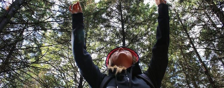 Woman in Woods Raised Hands