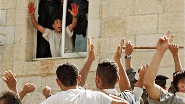 El linchamiento de dos reservistas israelíes en una estación de policía en Ramallah. Uno de los asesinos muestra a la multitud sus manos con sangre de las víctimas.